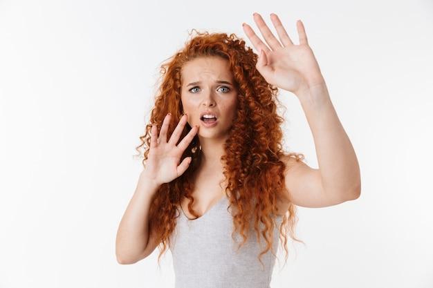 Portret atrakcyjnej przestraszonej młodej kobiety z długimi kręconymi rudymi włosami stojącej na białym tle