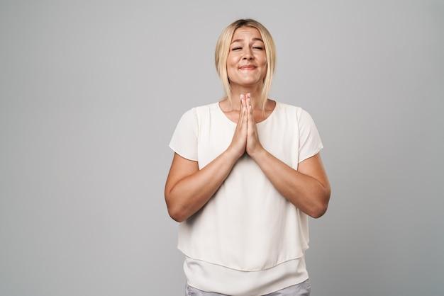 Portret atrakcyjnej przypadkowej kobiety stojącej odizolowanej nad szarą ścianą, modlącej się o