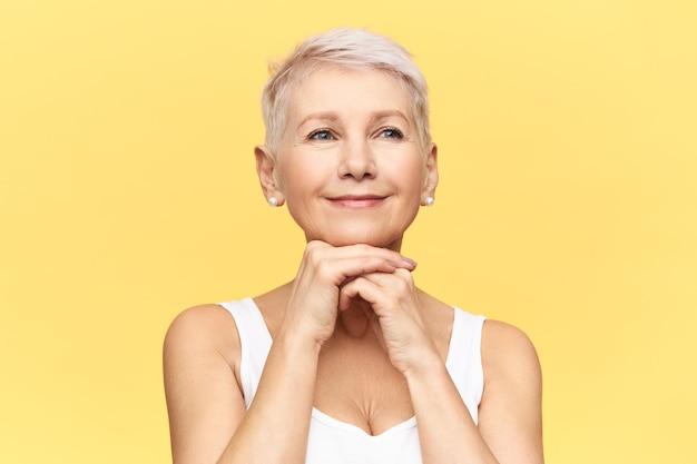Portret atrakcyjnej, radosnej kobiety w średnim wieku, z krótką stylową fryzurą i opaloną skórą, kładąc dłonie pod brodą, wykonując przeciwstarzeniowy lifting twarzy.