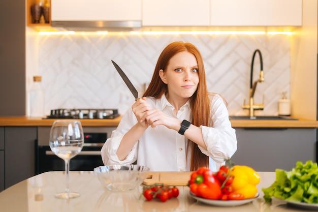Portret atrakcyjnej rudej młodej kobiety o szalonych oczach, trzymającej duży nóż siedzący przy stole z