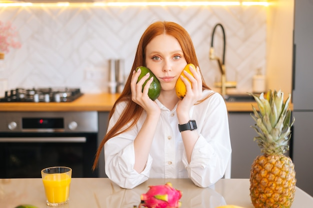 Portret atrakcyjnej rudej młodej kobiety trzymającej w rękach mango i awokado siedzącej przy stole z
