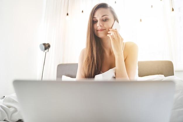 Portret atrakcyjnej skoncentrowanej blondynki młodej kaukaskiej kobiety siedzącej przed swoim komputerem