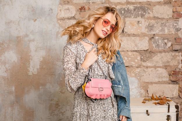 Portret atrakcyjnej stylowej blondynki kobiety w dżinsach i kurtce oversize chodzenia przed ścianą na ulicy
