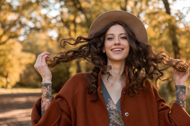 Portret atrakcyjnej stylowej uśmiechniętej kobiety z długimi kręconymi włosami spaceru w parku ubrana w ciepły brązowy płaszcz jesień modna moda, styl uliczny w kapeluszu