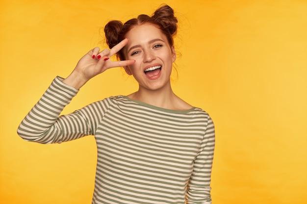 Portret atrakcyjnej, szczęśliwej dziewczyny rude włosy z dwoma bułeczkami. miała na sobie sweter w paski i pokazał znak pokoju nad okiem, wielki uśmiech. oglądanie na białym tle nad żółtą ścianą