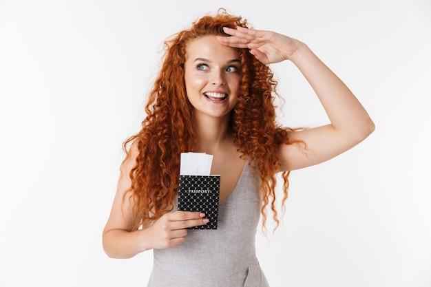 Portret atrakcyjnej, szczęśliwej młodej kobiety z długimi kręconymi rudymi włosami stojącej na białym tle, pokazującej paszport z biletami lotniczymi, patrzącej daleko
