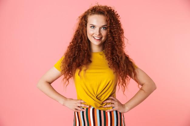 Portret atrakcyjnej szczęśliwej młodej kobiety z długimi kręconymi rudymi włosami stojącej na białym tle, ręce na biodrach