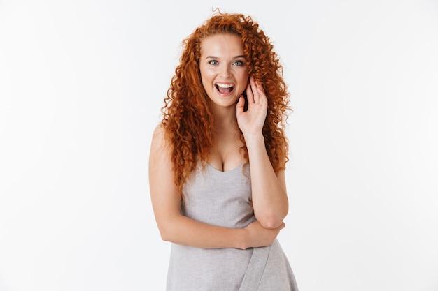 Portret atrakcyjnej szczęśliwej młodej kobiety z długimi kręconymi rudymi włosami stojącej na białym tle