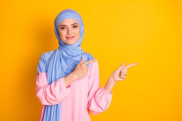 Portret atrakcyjnej treści wesołej muzułmanki noszącej hidżab, demonstrującej nową przestrzeń kopii nowości odizolowaną nad jasnożółtym kolorem tła