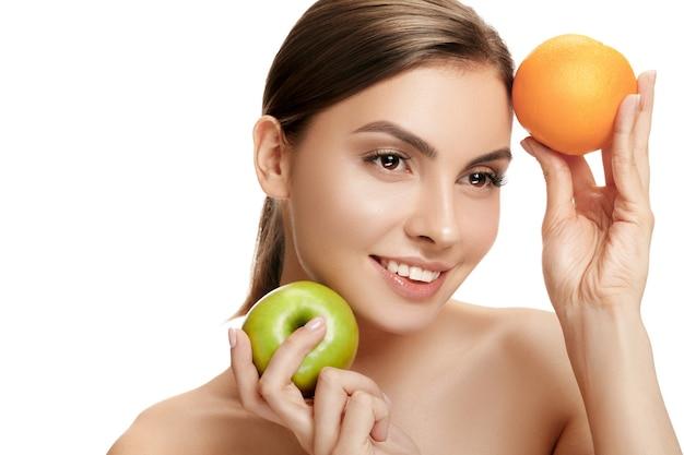 Portret atrakcyjnej uśmiechniętej kobiety na białej ścianie studia z zielonym jabłkiem i pomarańczowymi owocami