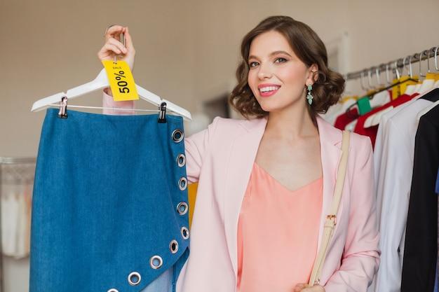Portret atrakcyjnej uśmiechniętej kobiety trzymającej spódnicę dżinsową na wieszaku w sklepie odzieżowym