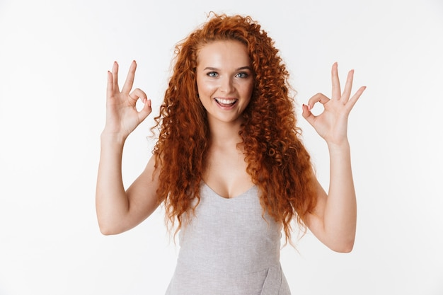Portret atrakcyjnej uśmiechniętej młodej kobiety z długimi kręconymi rudymi włosami stojącej na białym tle, pokazującej ok