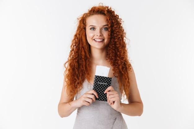 Portret atrakcyjnej uśmiechniętej młodej kobiety z długimi kręconymi rudymi włosami stojącej na białym tle, pokazującej paszport z biletami lotniczymi