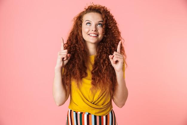 Portret atrakcyjnej uśmiechniętej młodej kobiety z długimi kręconymi rudymi włosami stojącej na białym tle, prezentującej miejsce na kopię