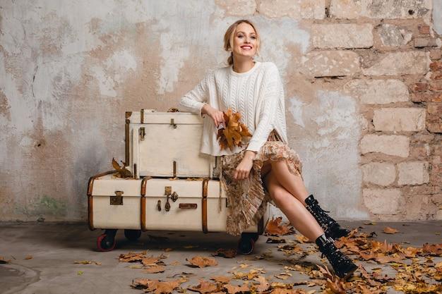 Portret atrakcyjnej uśmiechniętej stylowej blondynki kobiety w białym swetrze z dzianiny, siedzącej na walizkach na ulicy przed ściana