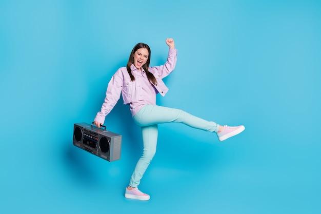 Portret atrakcyjnej wesołej dziewczyny nosi odtwarzacz muzyki tańczy na białym tle na niebieskim tle