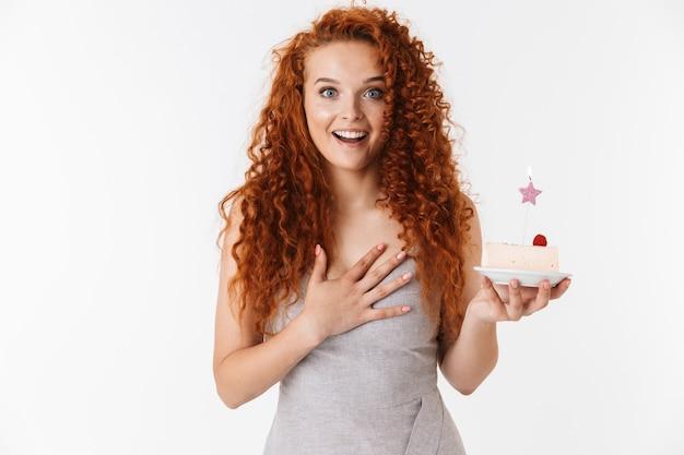 Portret atrakcyjnej wesołej młodej kobiety z długimi kręconymi rudymi włosami stojącej na białym tle, świętującej urodziny ciastem