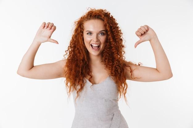 Portret atrakcyjnej, wesołej młodej kobiety z długimi kręconymi rudymi włosami stojącej na białym tle, wskazującej na siebie