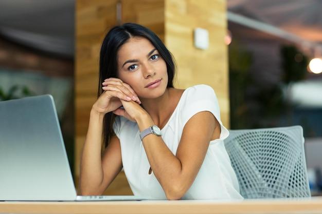 Portret atrakcyjnej zamyślonej bizneswoman siedzącej przy biurku w biurze