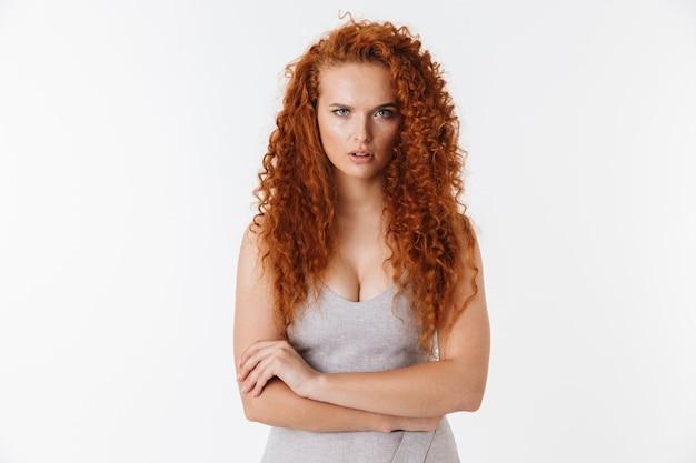 Portret atrakcyjnej zdenerwowanej młodej kobiety z długimi kręconymi rudymi włosami stojącej na białym tle, z założonymi rękami