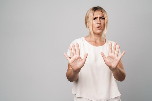 Portret atrakcyjnej zdezorientowanej kobiety stojącej odizolowanej nad szarą ścianą, pokazującej dłonie