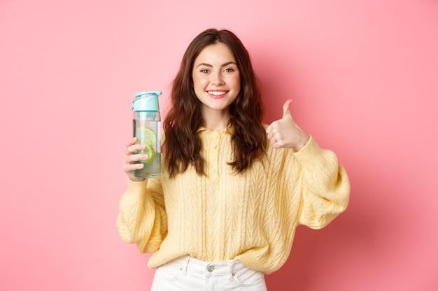 Portret atrakcyjnej zdrowej dziewczyny pokazując kciuki do góry i jej butelkę z wodą z cytryną, polecając napój dla twojego zdrowia, stojąc przed różową ścianą.