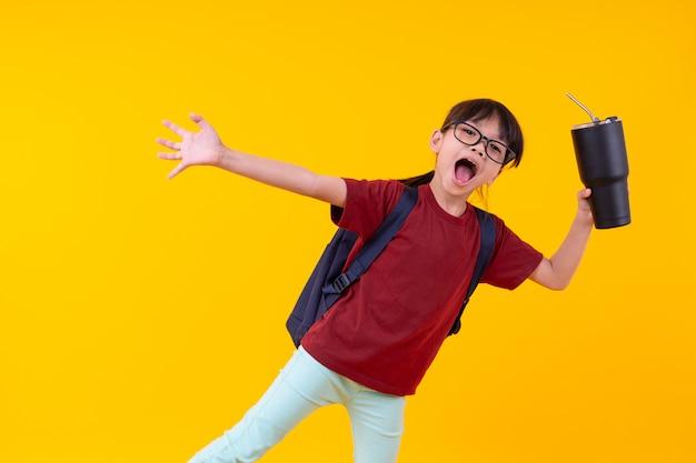 Portret atrakcyjny azjatycki dziewczyna uczeń trzyma szklankę wody na kolorze żółtym z szkolną torbą