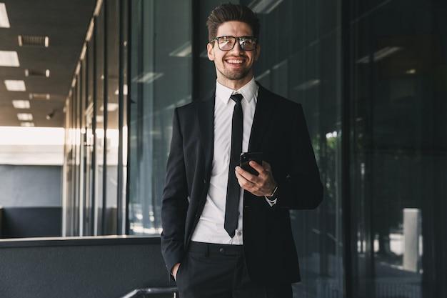 Portret atrakcyjny biznesmen ubrany w formalny garnitur stojący na zewnątrz budynku ze szkła i trzymając telefon komórkowy