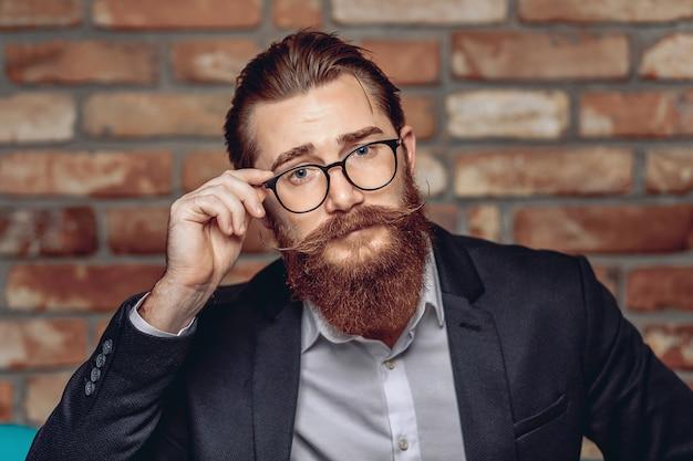 Portret atrakcyjny dorosły przystojny mężczyzna z wąsami i brodą, trzymając okulary i pozowanie na tle ściany z cegły. koncepcja męskiej urody