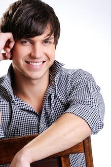 Portret atrakcyjny facet z toothy smily stwarzających w studio