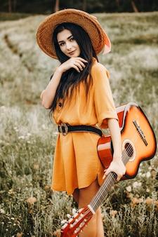 Portret atrakcyjny kaukaski kobieta trzyma gitarę i patrząc na kamery, uśmiechając się na wzgórzu z trawą i kwiatami.