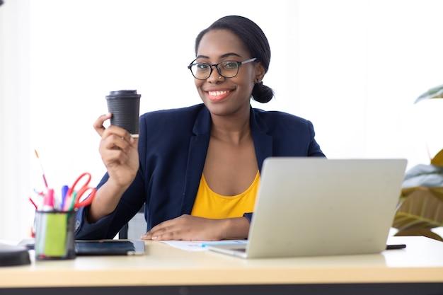 Portret atrakcyjny młody african american businesswoman picia czarnej kawy w nowoczesnym biurze domowym.
