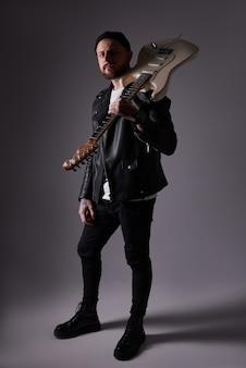 Portret atrakcyjny młody chłopak w skórzanej kurtce i tatuaże z gitarą elektryczną na ramieniu ciemne tło