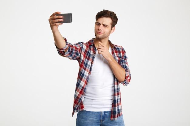 Portret atrakcyjny młody człowiek bierze selfie