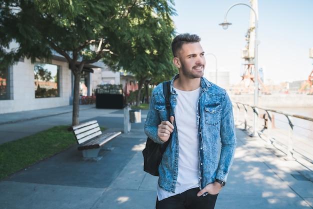 Portret atrakcyjny młody człowiek chodzenie po ulicy z plecakiem na ramionach