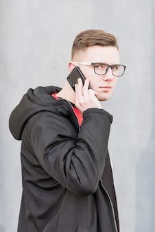 Portret atrakcyjny młody człowiek opowiada na telefonie komórkowym przeciw popielatemu tłu z okularami