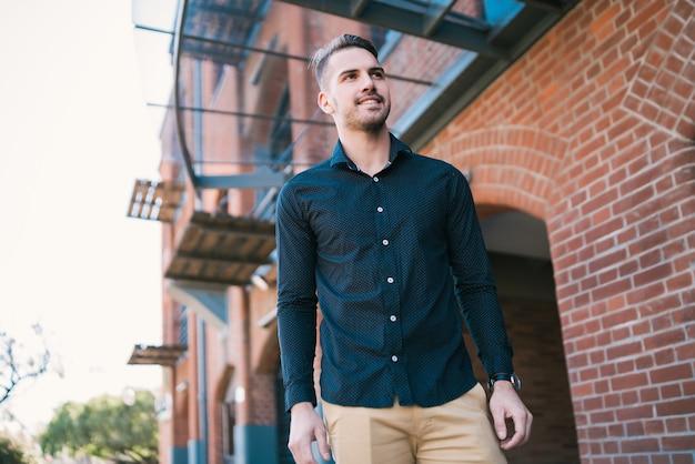 Portret atrakcyjny młody człowiek ubrany w ubranie, stojący na zewnątrz z przestrzeni miejskiej.