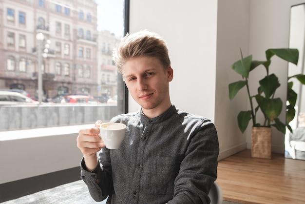 Portret atrakcyjny młody człowiek w lekkiej przytulnej kawiarni przy filiżance kawy