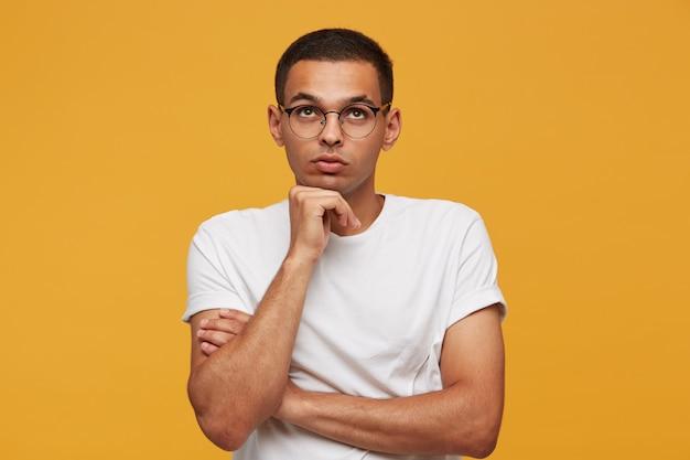 Portret atrakcyjny młody człowiek w okularach patrzy w górę rozważa myśl lub pomysł