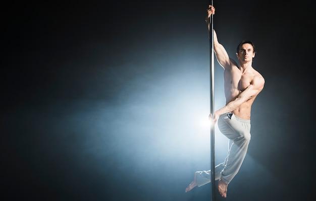 Portret atrakcyjny model mężczyzna wykonuje taniec na rurze