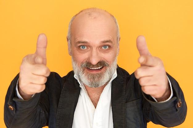 Portret atrakcyjny pozytywny biznesmen w średnim wieku z łysą głową i siwą brodą, wskazując palcami wskazującymi na aparat i uśmiechając się pewnie. sukces, kariera i pewność siebie. selektywna ostrość