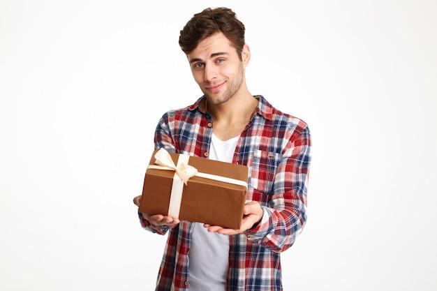 Portret atrakcyjny przypadkowy mężczyzna trzyma teraźniejszego pudełko