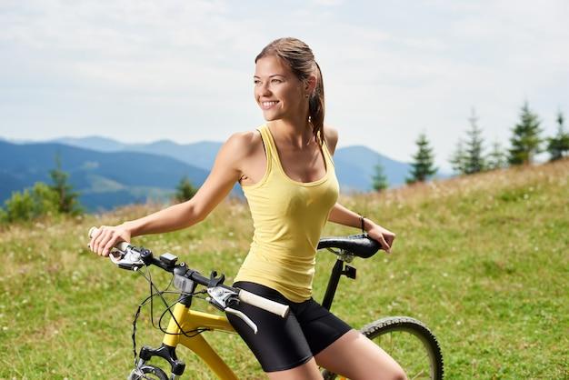 Portret atrakcyjny szczęśliwy kobieta rowerzysta odpoczywa na żółtym halnym bicyklu, cieszy się letniego dzień w górach. aktywność na świeżym powietrzu, koncepcja stylu życia