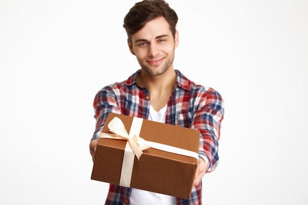 Portret atrakcyjny szczęśliwy mężczyzna pokazuje teraźniejszości pudełko