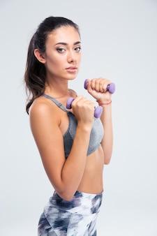Portret atrakcyjny trening fitness kobieta z hantlami na białym tle na białej ścianie