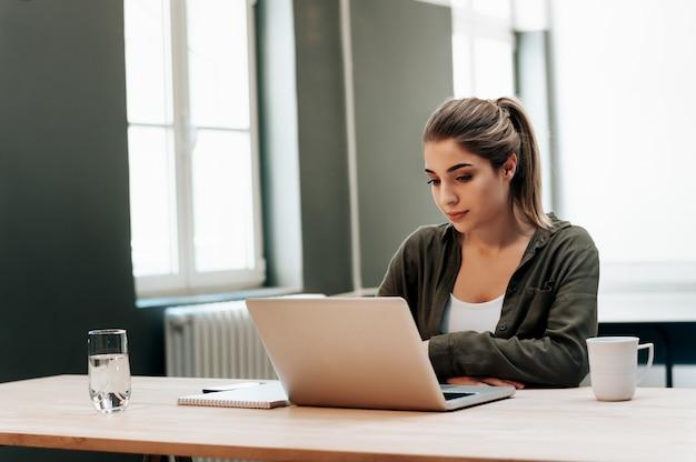 Portret atrakcyjny żeński uczeń używa laptop.
