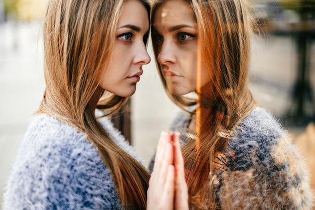 Portret autorefleksji niesamowitej młodej dziewczyny w lustrzanym oknie. niezwykła dziwna ładna kobieta o zmysłowej twarzy, która patrzy na siebie w gablocie. zmień ego. kobiecy stan umysłu. inne ja.