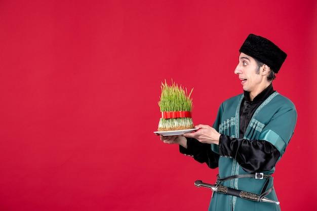 Portret azerskiego mężczyzny w tradycyjnym stroju dającego nasienie na czerwonym etnicznym wiosennym święcie novruz