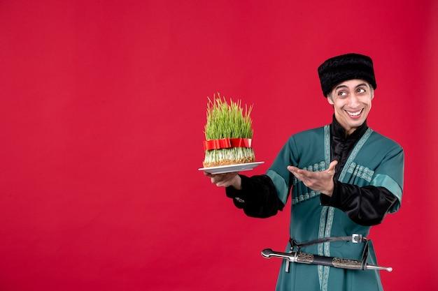 Portret azerskiego mężczyzny w tradycyjnym stroju dającego nasienie na czerwonym tancerzu etnicznym novruz wakacje wiosna