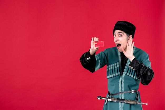 Portret azerskiego mężczyzny w tradycyjnym stroju trzyma studio karty kredytowej strzał czerwony novruz wiosenne pieniądze